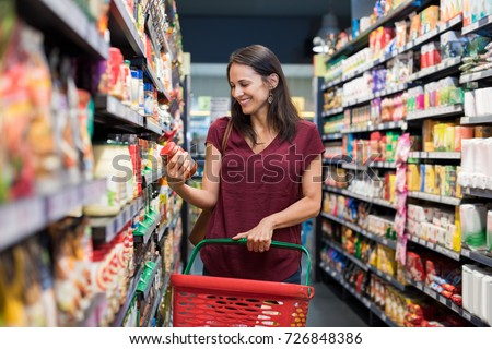 Happy mature woman looking at product at grocery store. Smiling hispanic woman shopping in supermarket and reading product information. Costumer buying food at the market. Royalty-Free Stock Photo #726848386