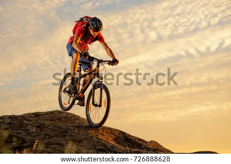 Cyclist in Red T-Shirt Riding the Bike Down the Rock on the Sunset Sky Background. Extreme Sport and Enduro Biking Concept. #726888628