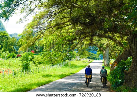 Two Men Cycling Down Road in Vinales Cuba #726920188