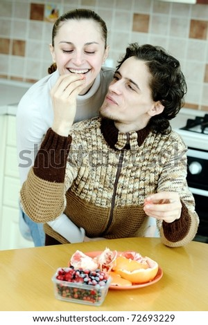 Funny scene of young happy couple playfully eating at kitchen #72693229