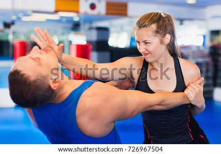 Bold positive  woman is training with man on the self-defense course in gym. Royalty-Free Stock Photo #726967504