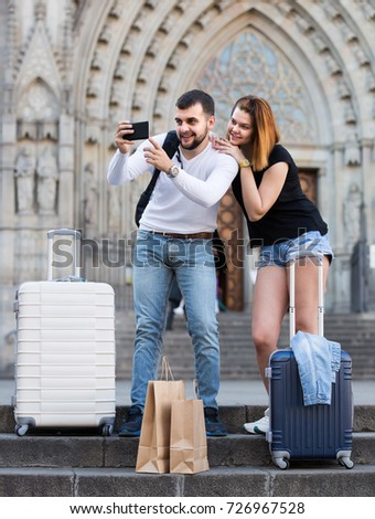 Smiling italian female and male standing with baggage at street and taking selfie  #726967528