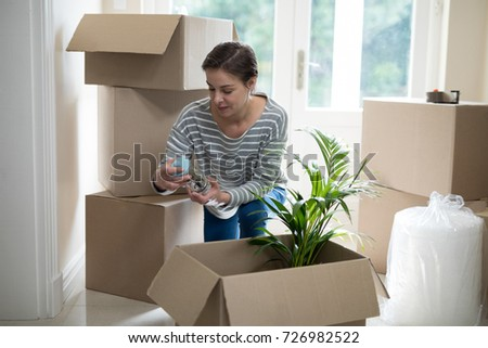 Woman opening cardboard boxes in living room at home #726982522