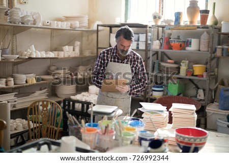Male potter maintaining record on clipboard in pottery workshop #726992344