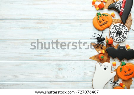 Halloween gingerbread cookies with candies on white wooden table
