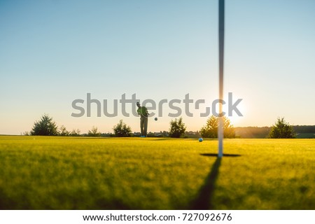 Full length view of the silhouette of a male player hitting a long shot on the putting green, of a professional golf course of a modern country club #727092676