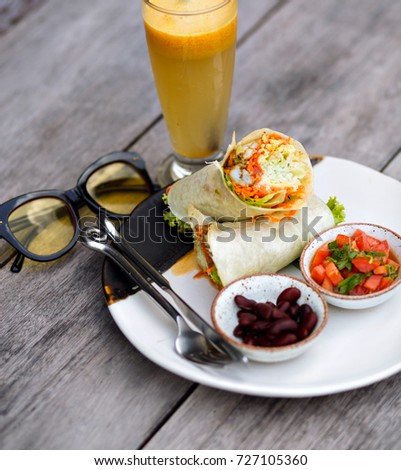 Photo of someone's dinner on wooden table beside glasses. Fruit juice standing near plate with vegetables, burrito and silver fork. #727105360