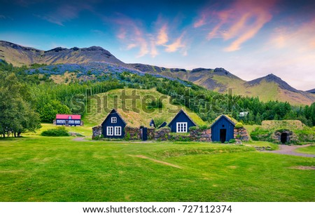 Typical view of Icelandic turf-top houses. Colorful summer sunrise in the Skogar village, south Iceland, Europe. Beauty of countryside concept background.