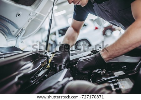 Cropped image of handsome mechanic in uniform is working in auto service. Car repair and maintenance. #727170871