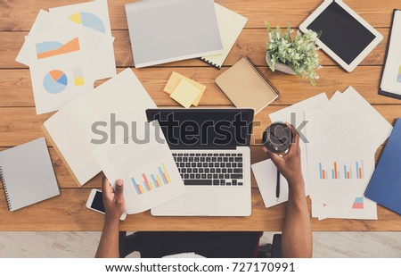 Office workspace top view. African-american businessman working at wooden desk, using laptop and various objects all around #727170991