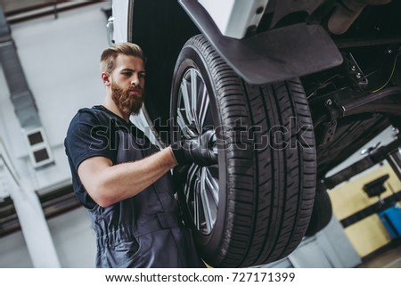 Handsome mechanic in uniform is working in auto service with lifted vehicle. Car repair and maintenance. Changing car wheel. #727171399