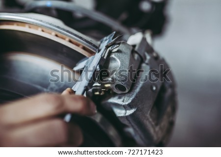 Cropped image of mechanic is working in auto service. Car repair and maintenance. Measuring the thickness of brake disc to identify its run-out. Royalty-Free Stock Photo #727171423