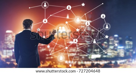 Back view of businessman against night cityscape working with social connection media concept #727204648