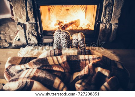 Feet in woollen socks by the Christmas fireplace. Couple sitting under the blanket, relaxes by warm fire and warming up their feet in woollen socks. Winter and Christmas holidays concept. #727208851