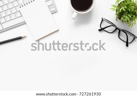 White office desk table with blank notebook, computer keyboard and other office supplies. Top view with copy space, flat lay. Royalty-Free Stock Photo #727261930