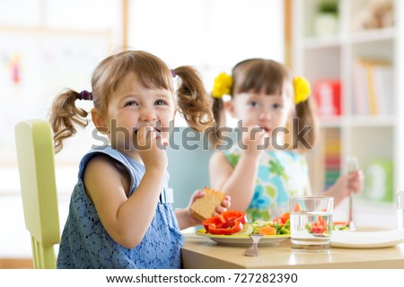 Cute little children eating food at daycare centre #727282390