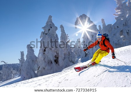 Skier skiing downhill in high mountains against blue sky #727336915
