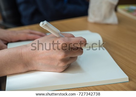 Hand of working or student woman holding a pen for write a message to a book or notebook on a wood table, business or education or journalism concept #727342738