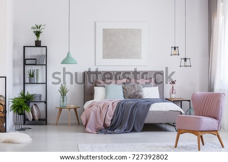 Retro pink chair in adorable pink bedroom with pastel bedding on bed and flowers in glass color vase on table #727392802