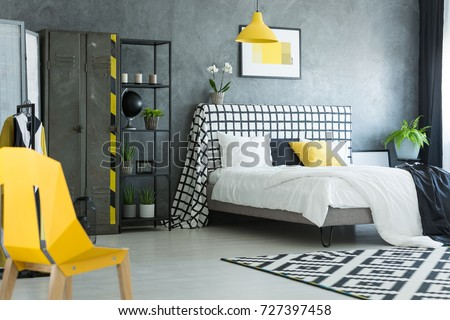 Yellow designer chair in black and white bedroom with geometric carpet and metal shelf #727397458
