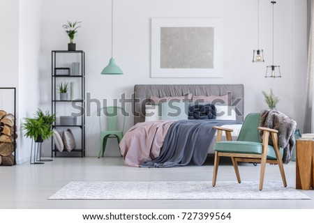 Mint chair next to king-size bed with pink and grey bedsheets in cozy bedroom with wooden elements #727399564
