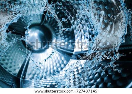Water splash of the washing machine drum Royalty-Free Stock Photo #727437145