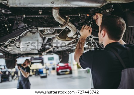 Two handsome mechanics in uniform are working in auto service with lifted vehicle. Car repair and maintenance. Royalty-Free Stock Photo #727443742