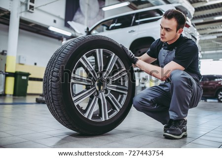 Handsome mechanic in uniform is working in auto service. Car repair and maintenance. Holding car wheel. #727443754