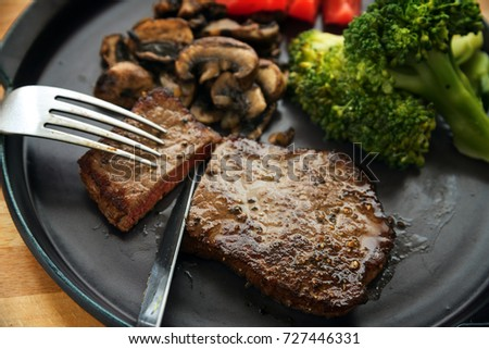 beef steak is cut with knife and fork, with vegetables like broccoli, mushrooms and tomatoes, low carb diet dinner on a dark gray plate, selected focus, narrow depth of field Royalty-Free Stock Photo #727446331