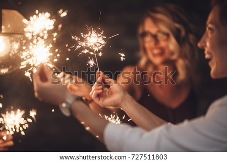 Group of happy people holding sparklers at party and smiling. #727511803