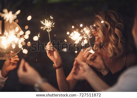 Group of happy people holding sparklers at party and smiling. #727511872