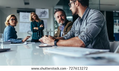 Businessman explaining new business ideas to peers. Business people discussing in board room. Royalty-Free Stock Photo #727613272