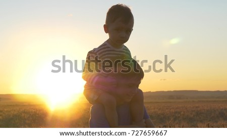 Two boys playing at sunset in a wheat field among golden spikelets #727659667