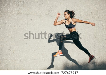 Young woman with fit body jumping and running against grey background. Female model in sportswear exercising outdoors. Royalty-Free Stock Photo #727673917