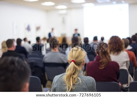 Business and entrepreneurship symposium. Female speaker giving a talk at business meeting. Audience in conference hall. Rear view of unrecognized participant in audience. Copy space on whitescreen. #727696105