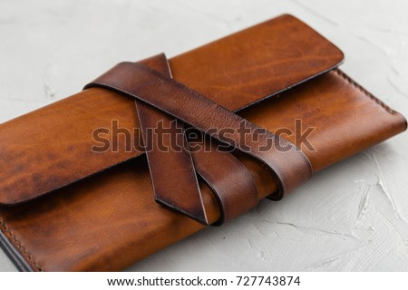 Stylish handmade brown leather wallet on gray background Royalty-Free Stock Photo #727743874