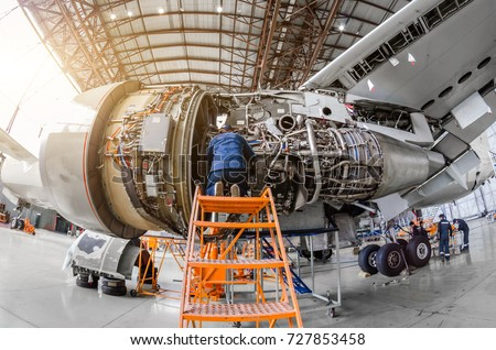 Specialist mechanic repairs the maintenance of a large engine of a passenger aircraft in a hangar Royalty-Free Stock Photo #727853458