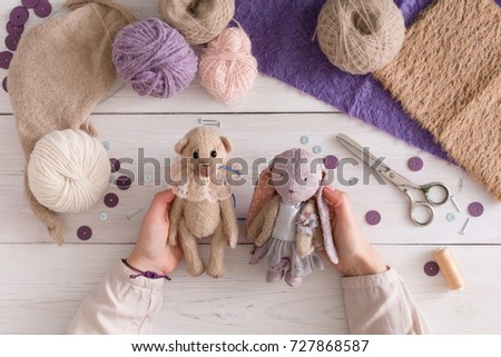 Process of making vintage toy, top view. Artisan pov, needlewoman hands holding handmade teddy bear and rabbit, home workshop #727868587