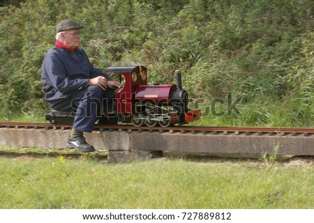 23rd September 2017- A man driving a miniature steam engine at a show organised by the Llanelli & District Model Engineers Club in Pembrey Country Park, Carmarthenshire, Wales, UK. #727889812