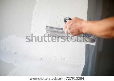 Construction worker with long trowel plastering a wall. #727913284
