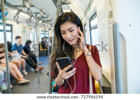 Asian woman passenger with casual suit using and listening the song via smart mobile phone in the Skytrain rails or subway for travel in the big city, lifestyle and transportation concept #727966594