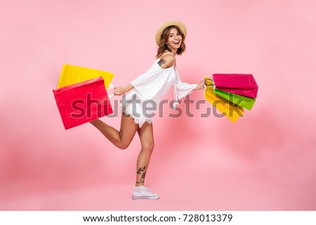 Full length portrait of a happy pretty girl holding shopping bags while running and looking at camera isolated over pink background #728013379
