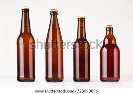 Collection different brown beer bottles, mockup. Template for advertising, design, branding identity on white wood table. Royalty-Free Stock Photo #728090896