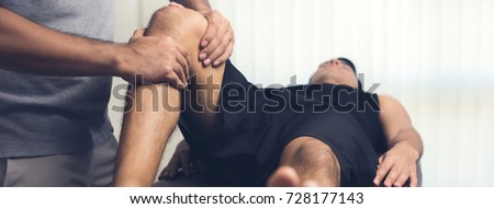 Therapist treating injured knee of athlete male patient - sport physical therapy concept, panoramic banner