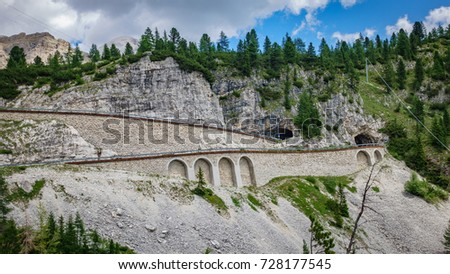 Wide angle view of Falzarego pass curve with tunnel, profile view #728177545