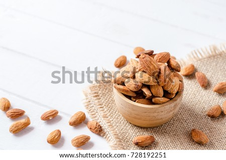 Almonds in bowl on white wooden background #728192251