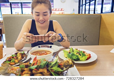 Smiling asian women taking a picture of food on her mobile phone in restaurant.