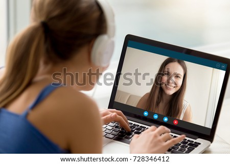 Two female friends chatting via video conference application. Woman in headphones talking to long distance friend. Foreign language exchange, virtual communication, international friendship concept. #728346412