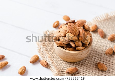 Almonds in bowl on white wooden background #728363419
