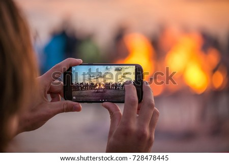 Woman is taking picture of sunset with smart phone. Romantic bonfire night at seaside. People gathering together to celebrate Night of ancient lights. Large burning campfire with soft glowing flame